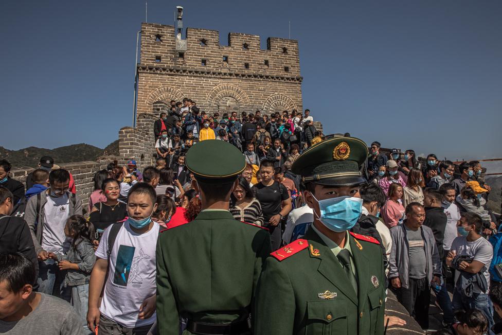 جنود صينيون في نوبة حراسة أثناء زيارة سياح أجانب لسور الصين العظيم.