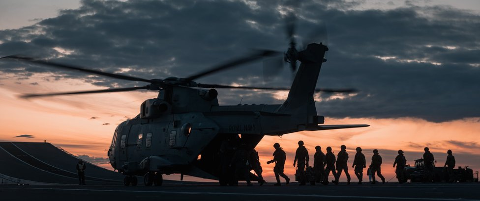 The silhouette of Royal Marines with a helicopter