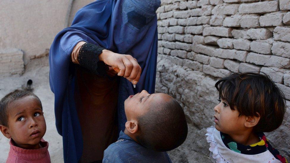 Una mujer en Afganistán con un atuendo tradicional, burka, que cubre su rostro, pone gotitas de la vacuna oral de polio en la boca de un niño.