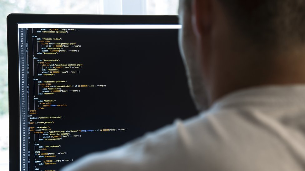 A coder looks at a computer