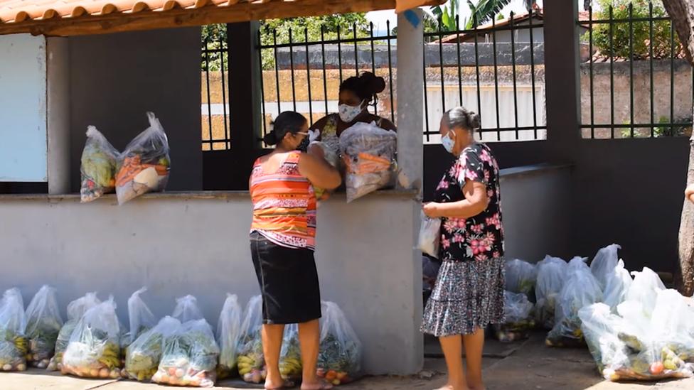 Uma mulher entrega e duas recebem cestas básicas em ação de doação promovida pelo Centro de Agricultura Alternativa do Norte de Minas