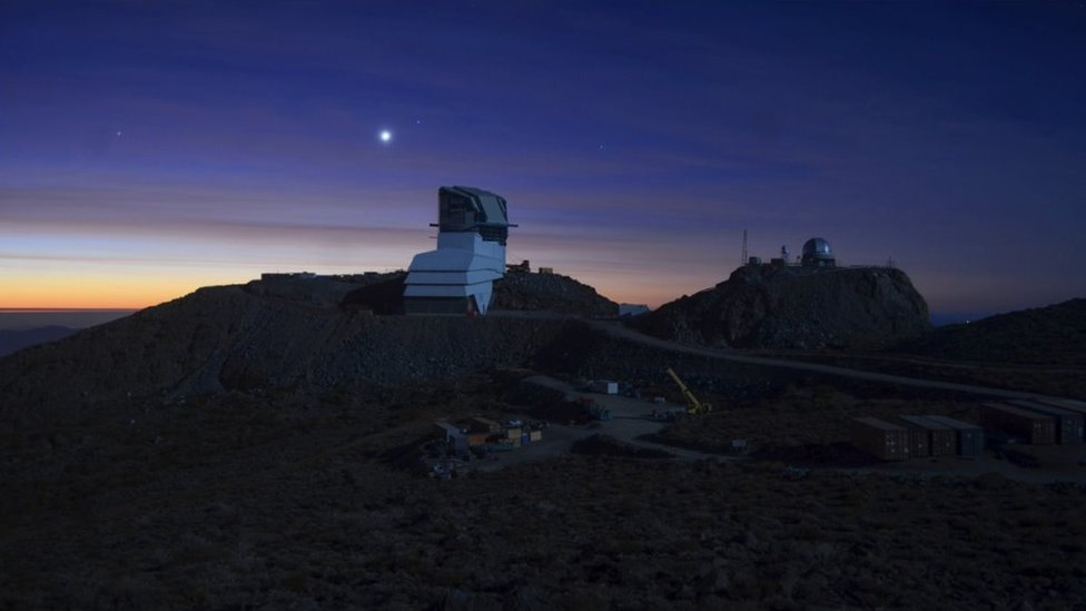 Rubin Observatory at sunset, lit by a full moon.