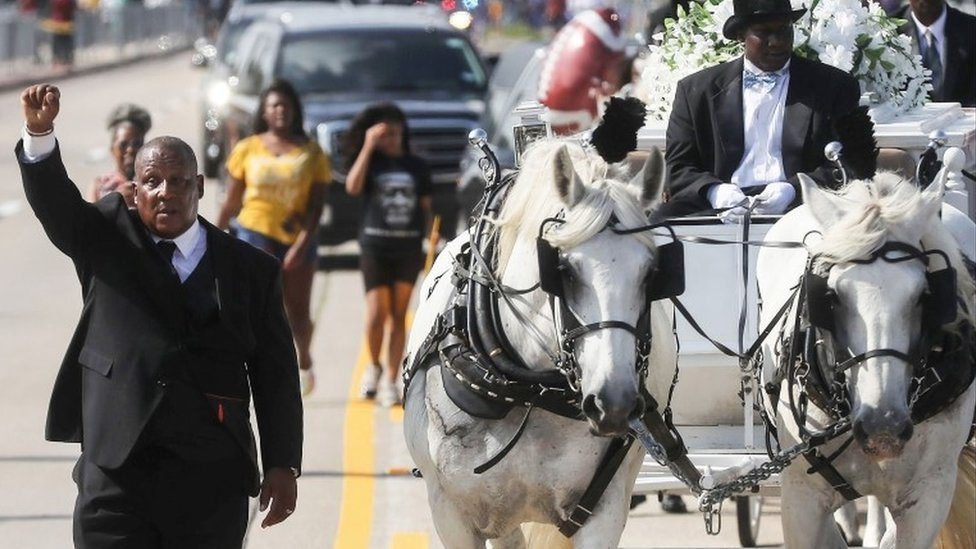 A man holds his hand up in solidarity as the remains of George Floyd are brought by horse-drawn carriage in a funeral procession to Houston Memorial Gardens Cemetery for burial on June 9, 2020 in Pearland, Texas