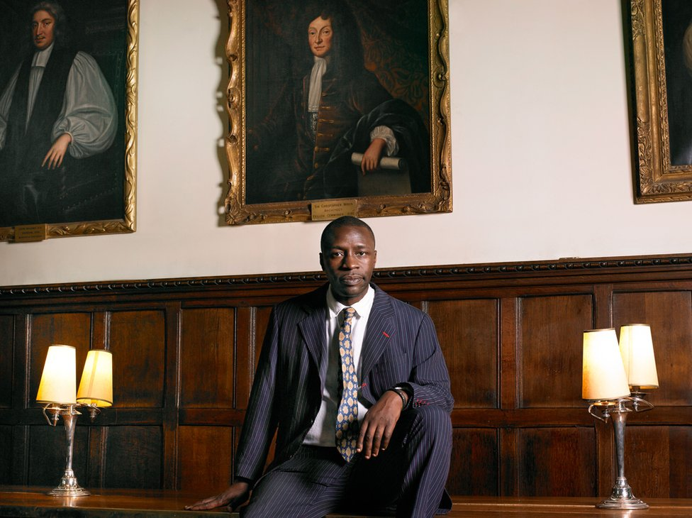 Portrait of British writer Diran Adebayo standing in front of paintings on the wall