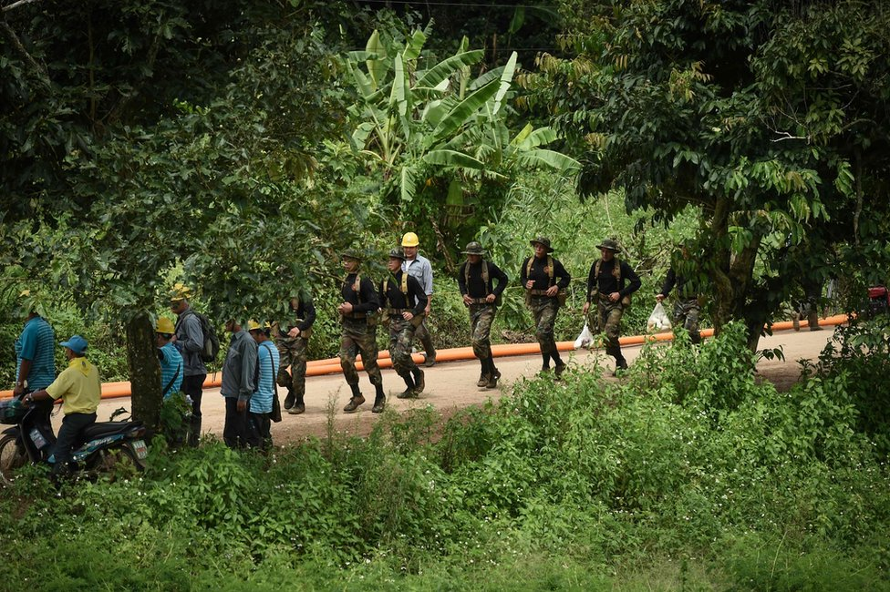 Thai soldiers run down the road leading to the Tham Luang cave