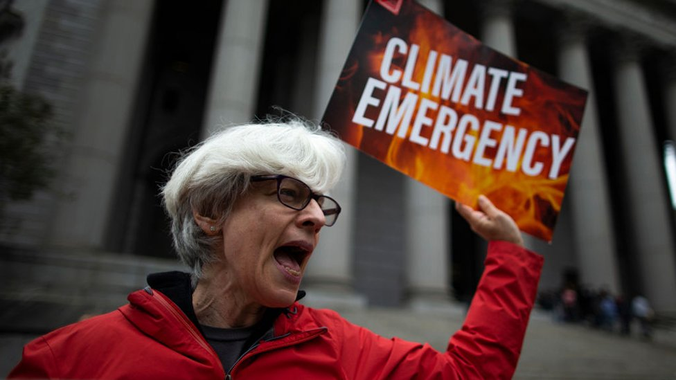 A climate change protester outside the New York State Supreme Court building on the first day of the ExxonMobil trial on 22 October, 2019