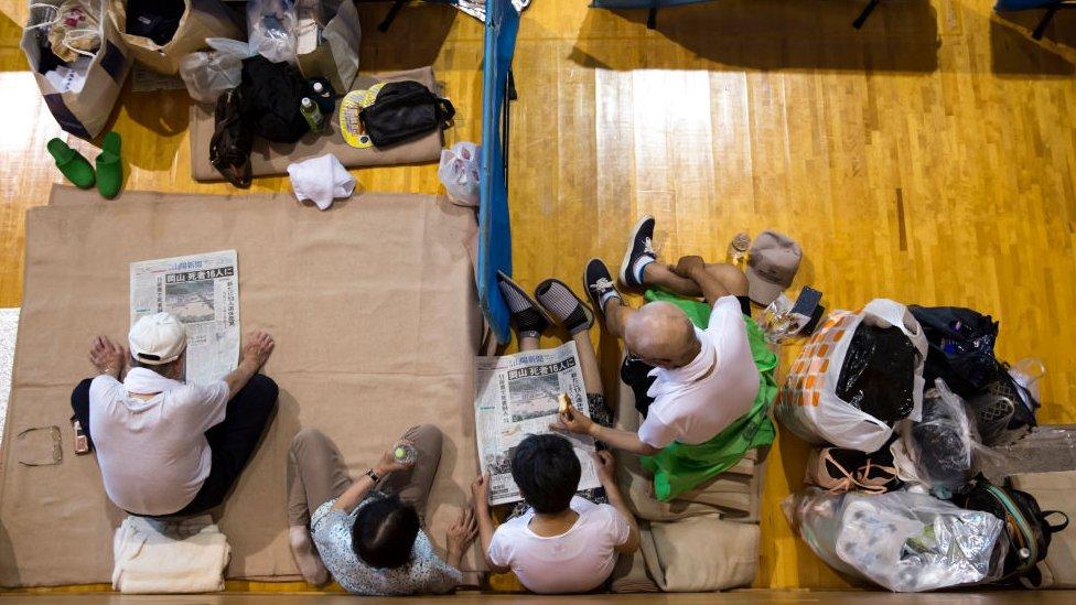 Evacuees read newspapers in a gymnasium used as an evacuation centre on July 9, 2018 in Kurashiki, Okayama