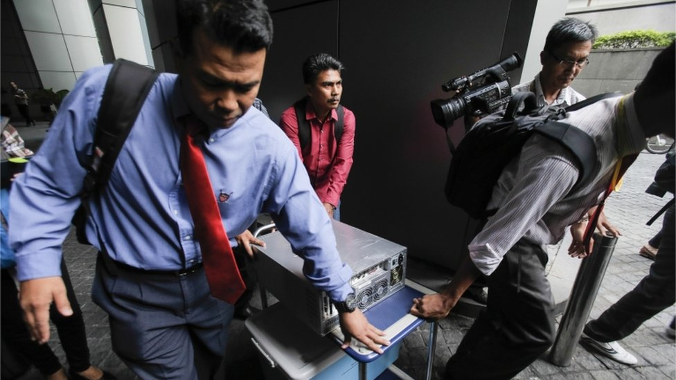 Malaysian plainclothes police carry a computer from the 1MDB (1 Malaysia Development Berhad) office after a raid in Kuala Lumpur, Malaysia, Wednesday, July 8, 2015.