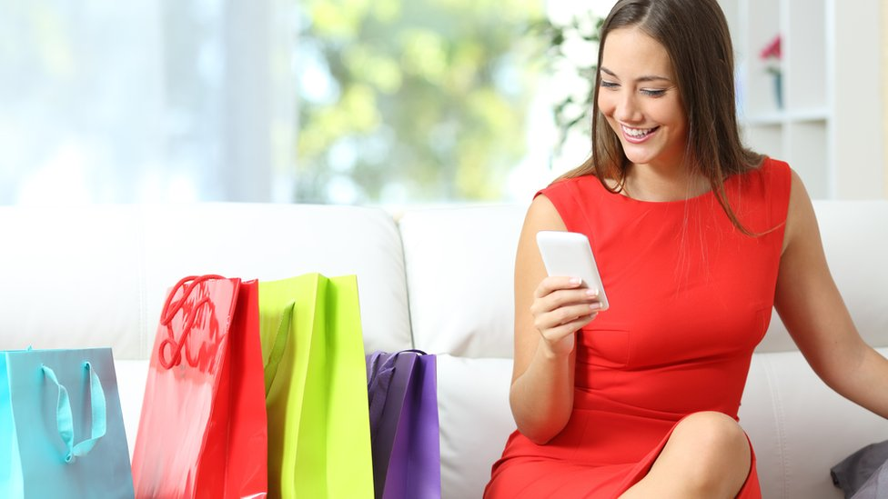 Woman on smartphone with shopping bags