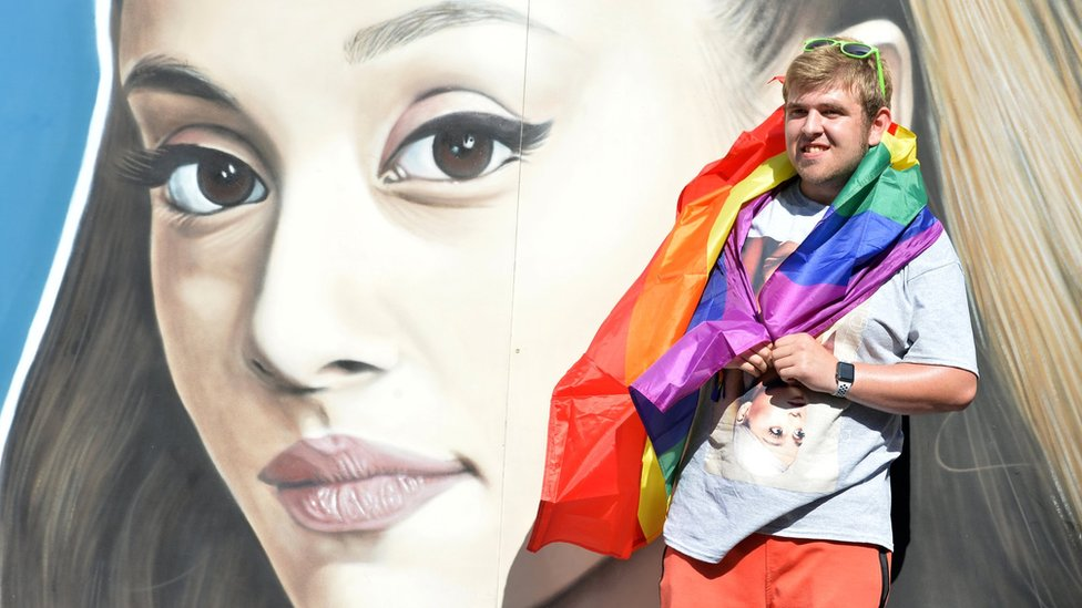A Pride reveller in front of a mural of Ariana Grande's face in Manchester