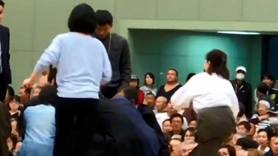 A photo grab from a Youtube video shows women climbing up a sumo ring to treat Maizuru city mayor Ryozo Tatami, who collapsed while making a speech in a gym in Maizuru, Kyoto prefecture, Japan April 4,