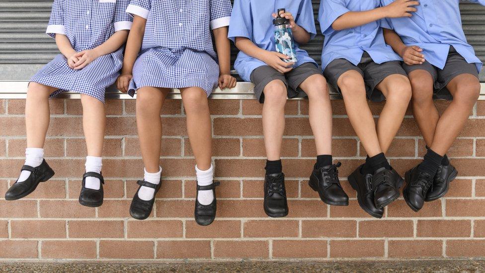 Piernas de niñas y niños en edad escolar llevando uniforme.