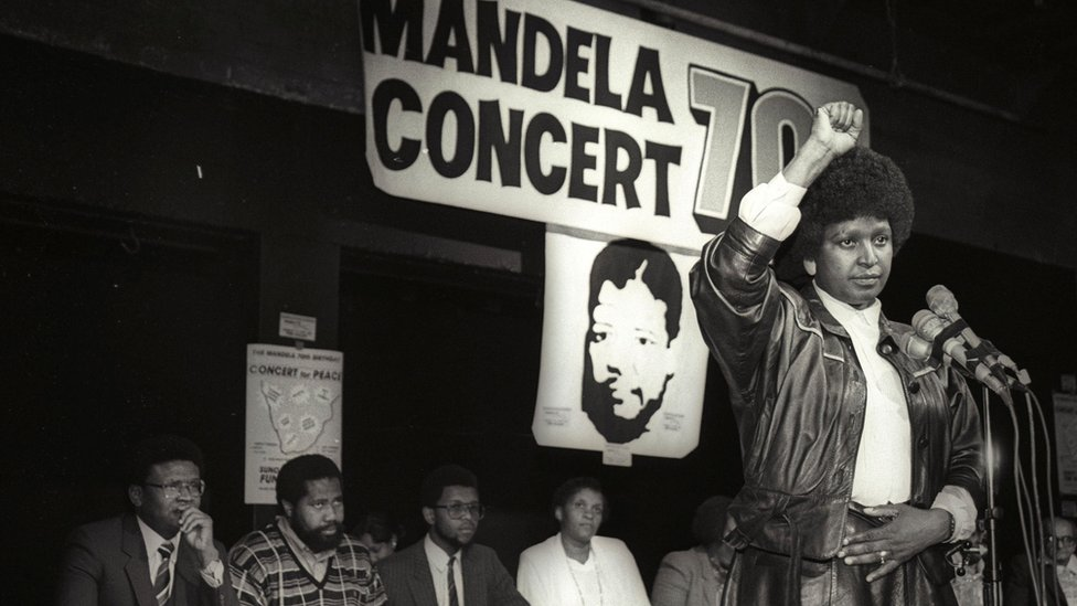 Winnie Mandela raises her fist in a black power salute after announcing that a massive pop concert will be held to mark the 70th birthday of her husband in 1988