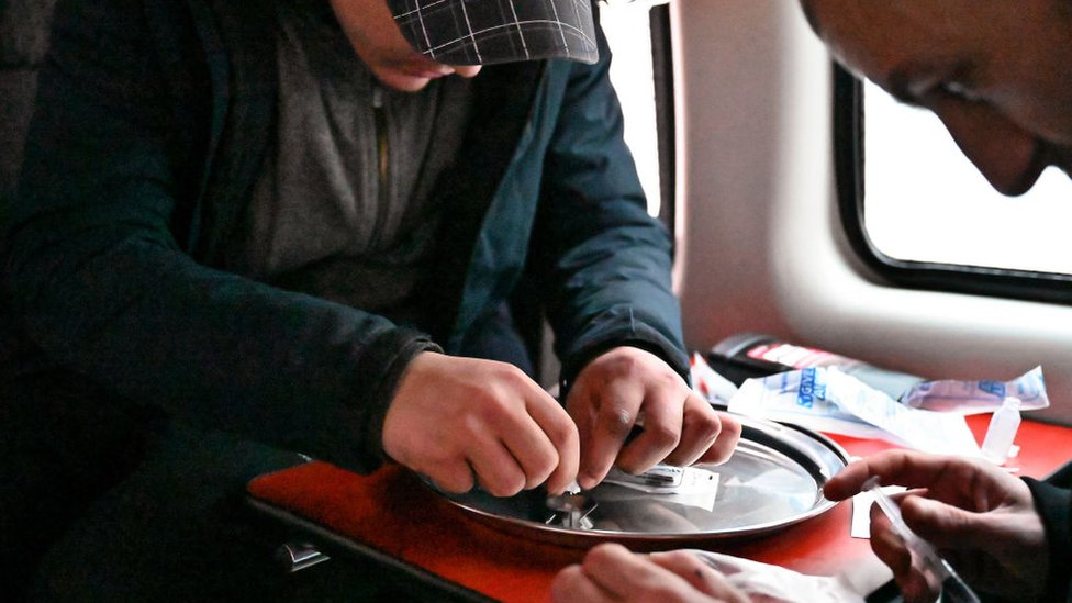 Dos consumidores preparan la cocaína antes de inyectarse, dentro de una camioneta de consumo segura creada por un exadicto en recuperación.