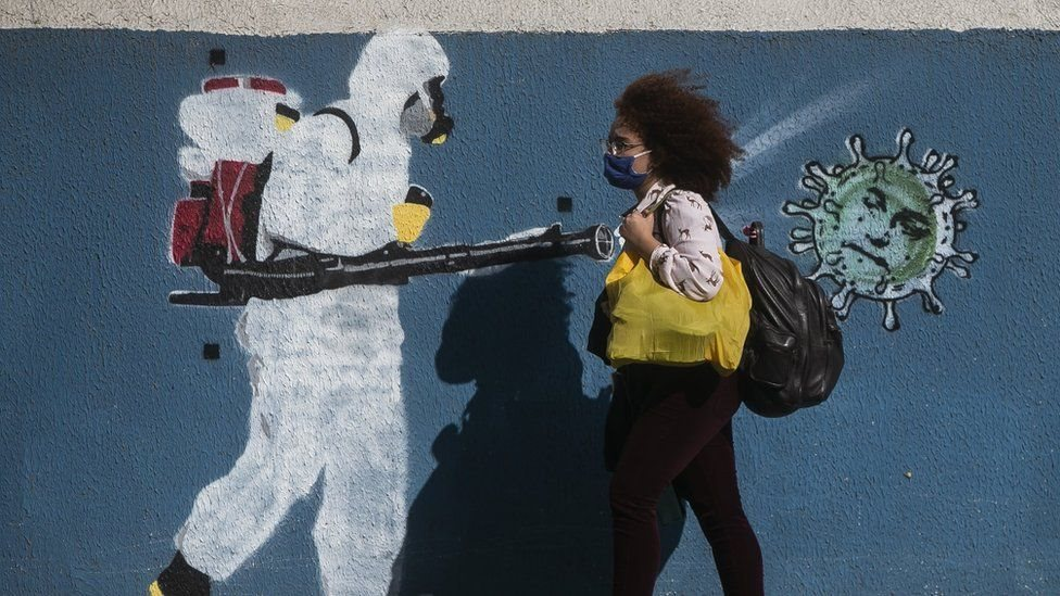 A woman in a mask walking next to a graffiti of a public health worker.