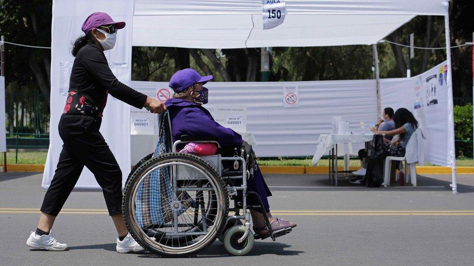 Una mujer acompaña a otra en silla de ruedas para votar en Perú