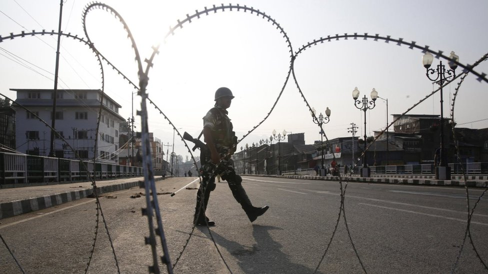 Indian military in front of barbed wire fence