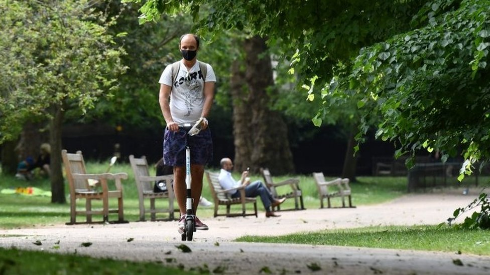 A man rides an electric scooter through St James' Park in central London