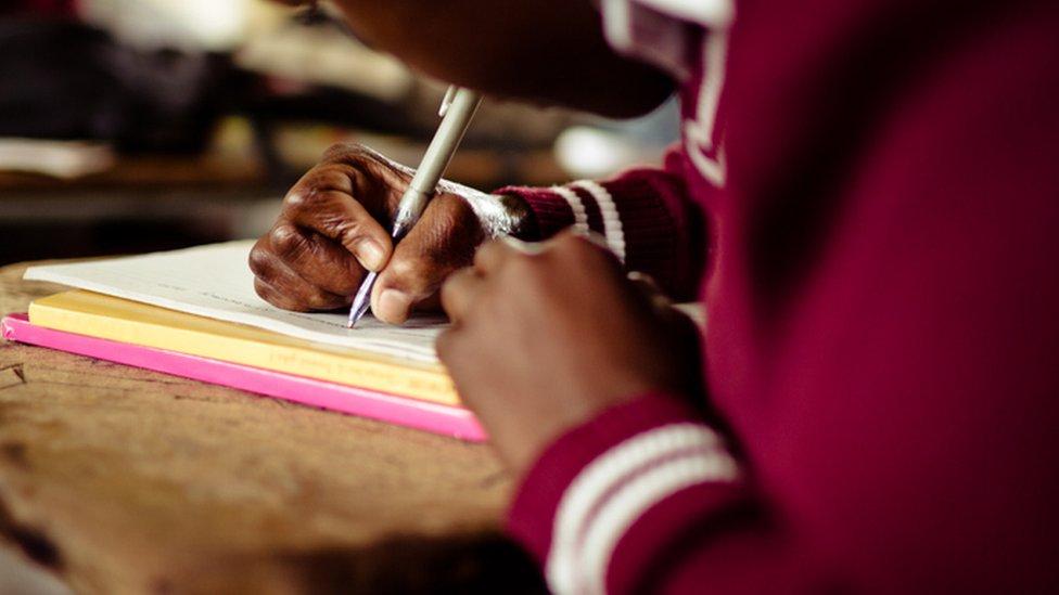 Criança escrevendo em caderno