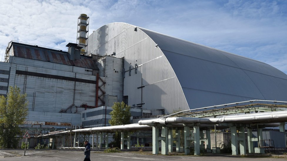 A man walks next to the New Safe Confinement over the fourth block of the Chernobyl nuclear plant in Chernobyl on 5 October 2018