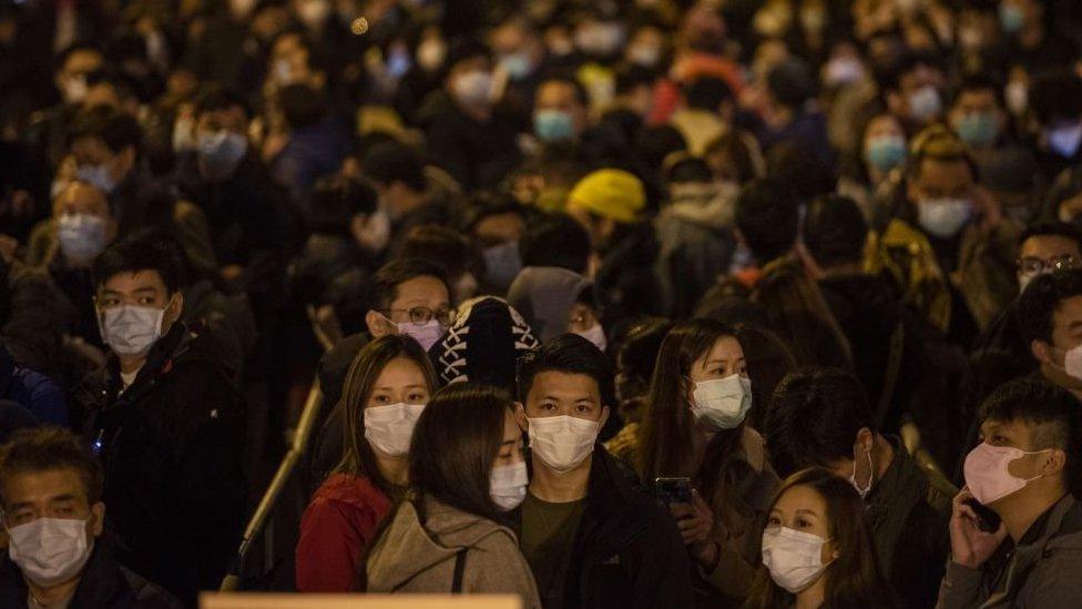 حشد من الناس في هونغ كونغ يرتدون أقنعة أوجه