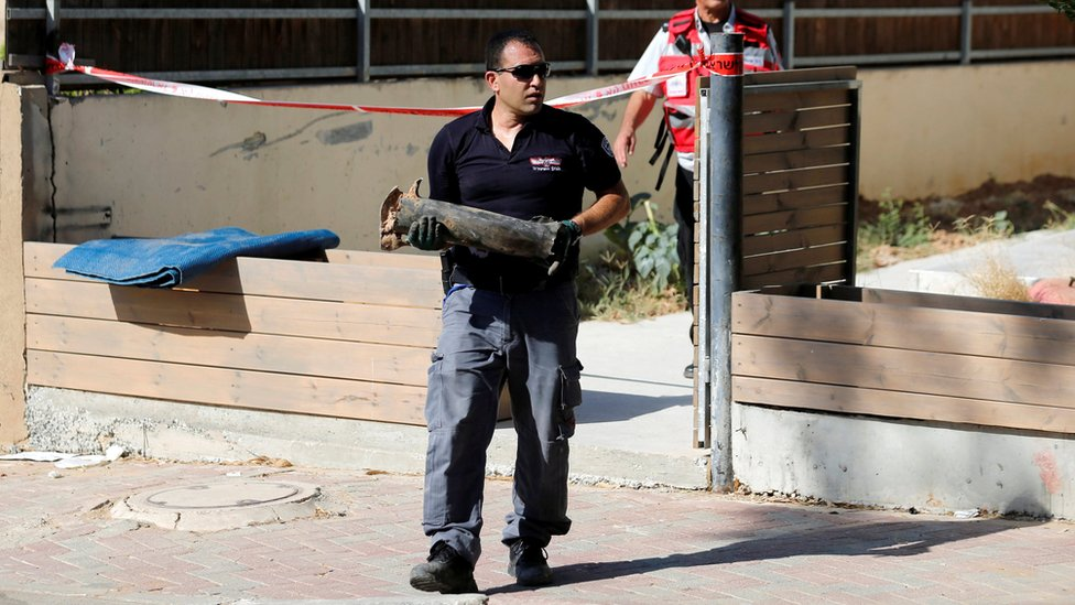 An Israeli policeman carries part of a rocket which the Israeli army said was launched from Gaza at the Israeli town of Sderot (21 August 2016)