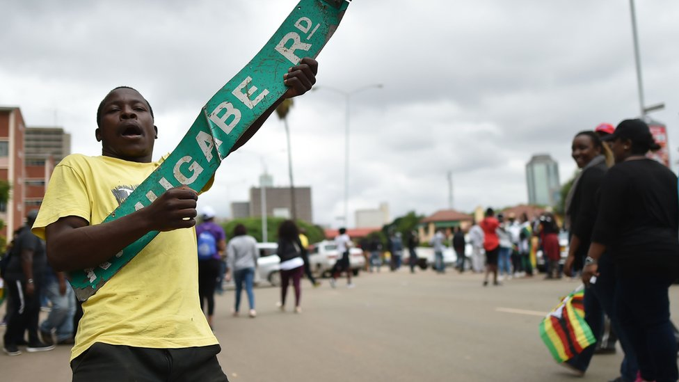 A man reacts with a sign reading 'Robert Mugabe Road' during a demonstration marching towards the State House while demanding the resignation of Zimbabwe's president on November 18, 2017 in Harare