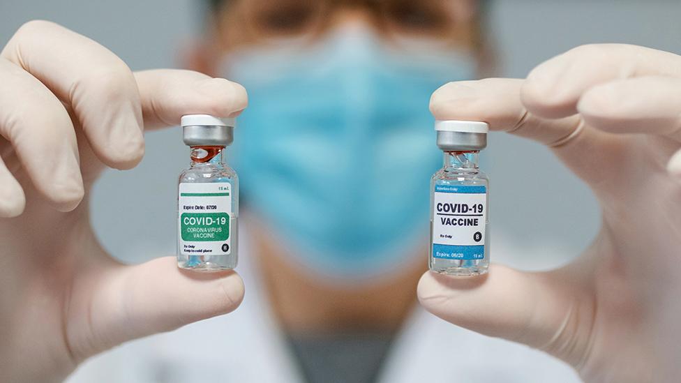 Médica mostrando dos opciones de vacuna contra el coronavirus