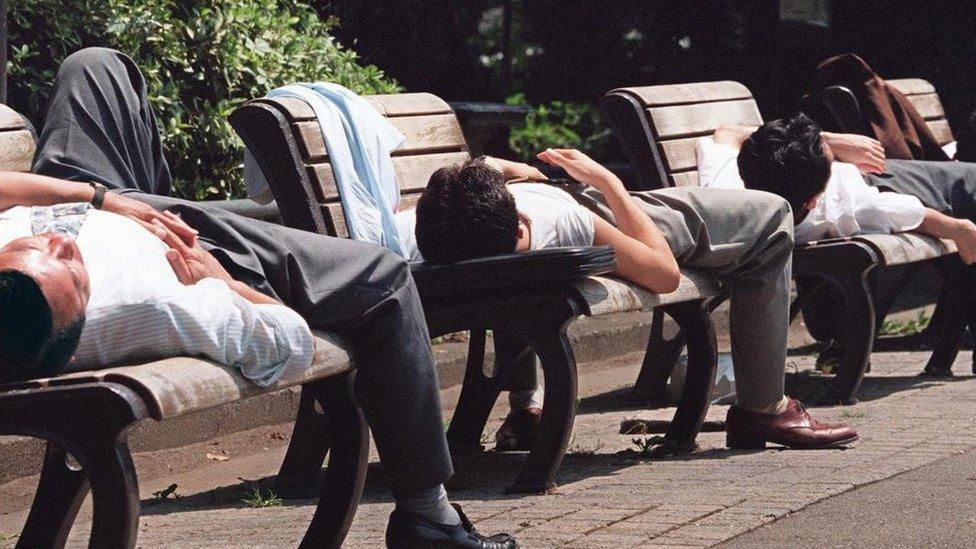 Men sleeping in benches