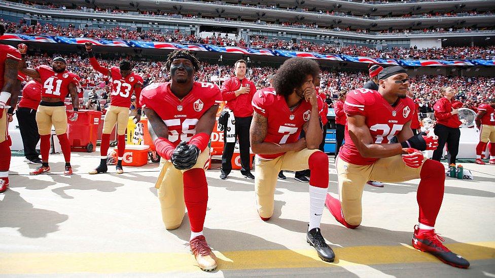 Kaepernick y sus compañeros durante el himno de los Estados Unidos.