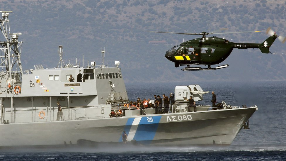 A Frontex helicopter and a Greek Coast guard vessel stop a dinghy with a suspected smuggler aboard off the Greek island of Lesbos
