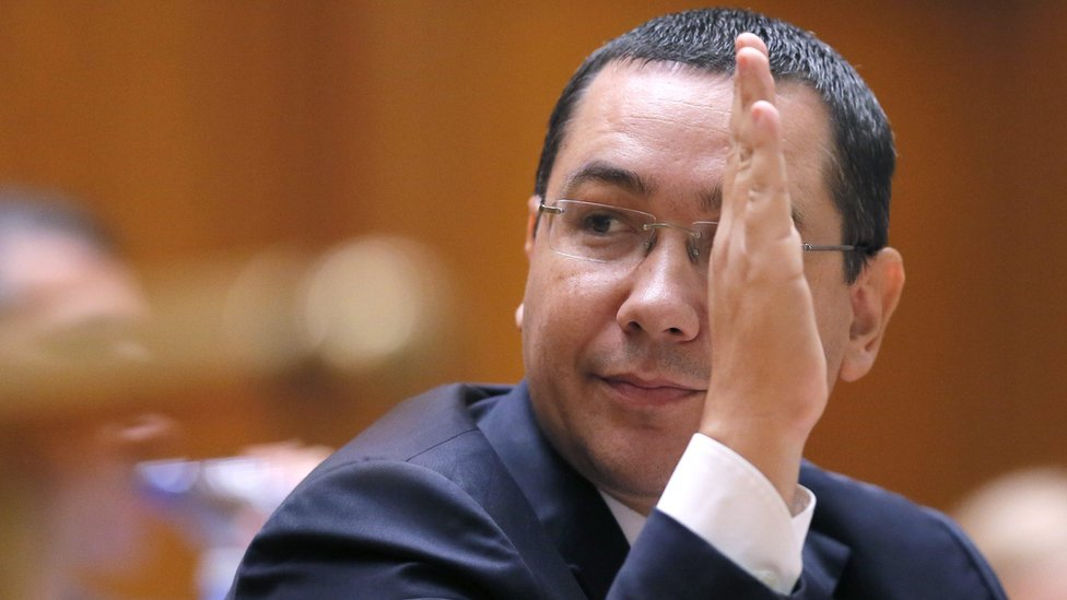 Romanian Prime Minister Victor Ponta raises his hand during a speech in front of both parliament chambers during no-confidence motion procedures
