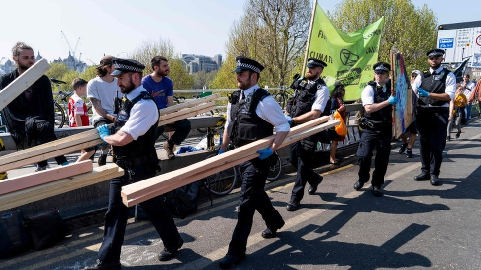 Officers carry away pieces of wood as they break up the climate change activist's camp on Waterloo Bridge