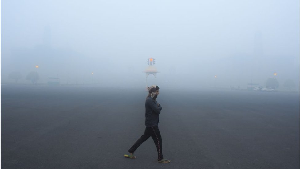 A man walking in Delhi as heavy smog shrouds buildings in the city