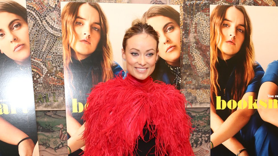 Booksmart director Olivia Wilde standing in front of posters for the film