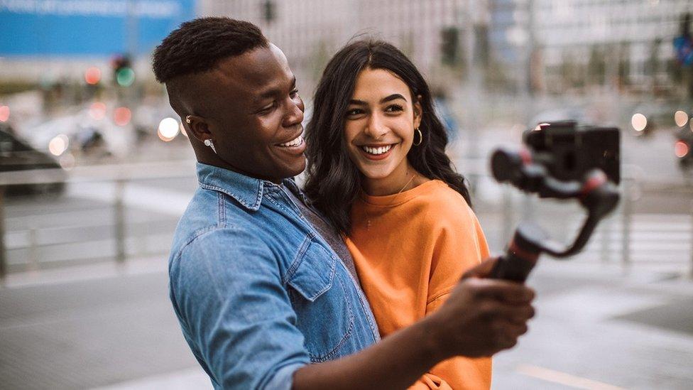 Una pareja sonriendo a una cámara