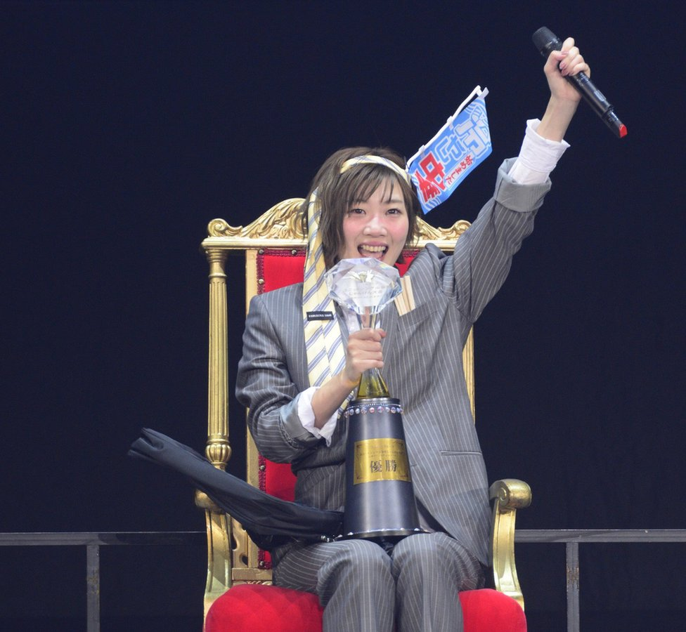 Miku Tanabe in a grey pin-stripe suit with a neck tie around her head, seated on a red throne-like chair and with a trophy on her lap.