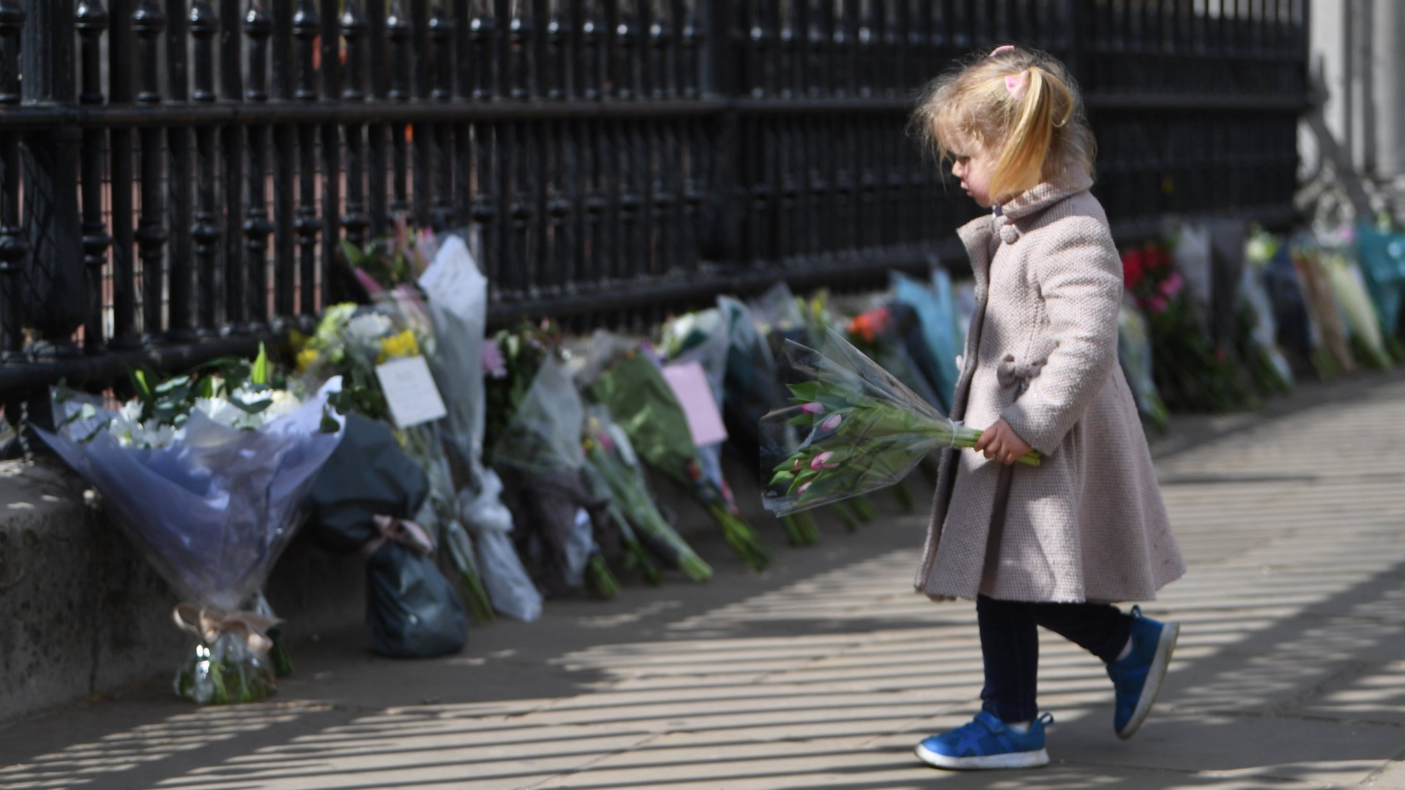 A young girl holds flowers outside Buckingham Palace on 9 April 2021