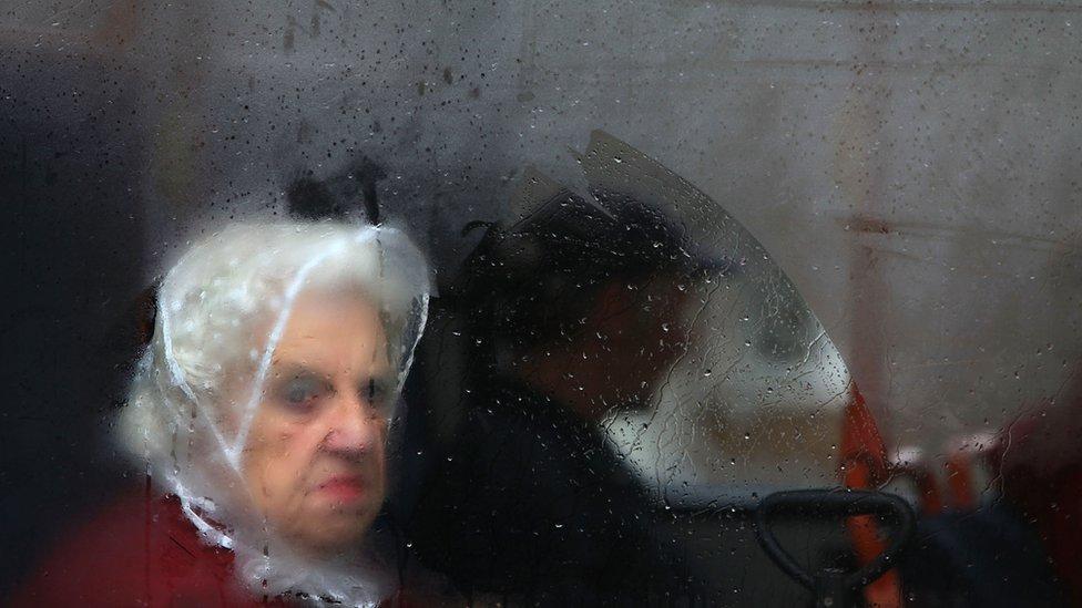 Žena gleda kroz zamagljen prozor