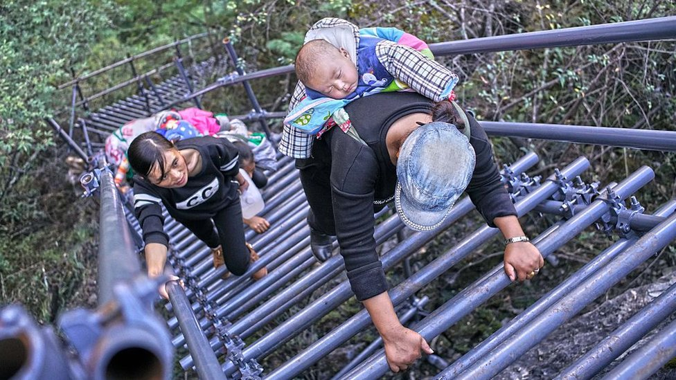 People climb on the newly-built metal ladder with hand railings to Ahtuler village on a cliff on November 11, 2016