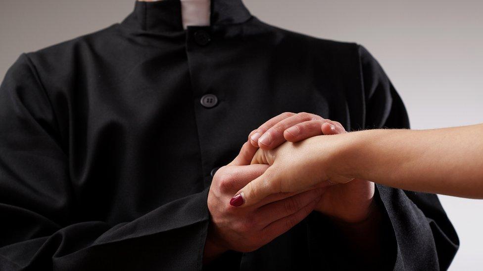 sveštenik drži žensku ruku