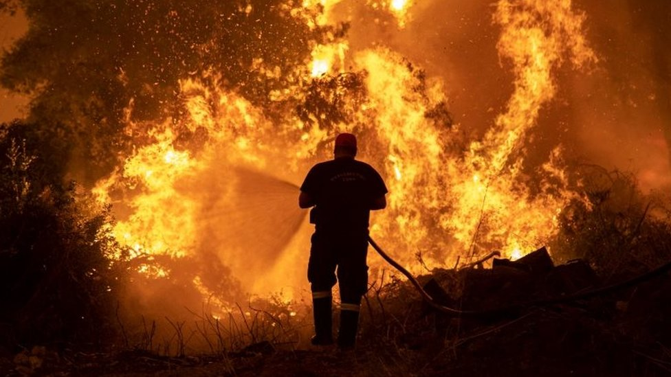 A firefighter tries to extinguish a wildfire burning in the village of Pefki
