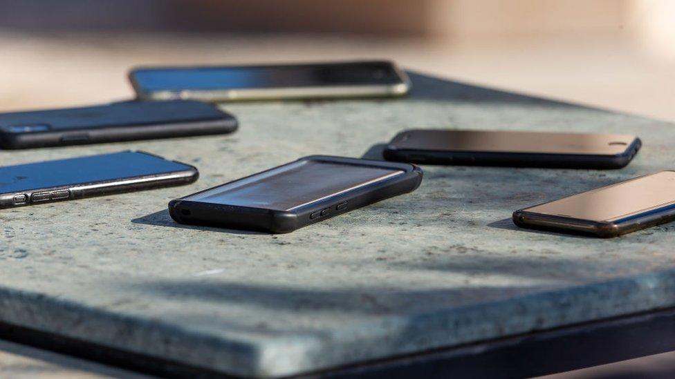 Varios celulares en una mesa.