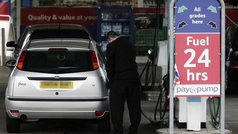 man fills car with petrol
