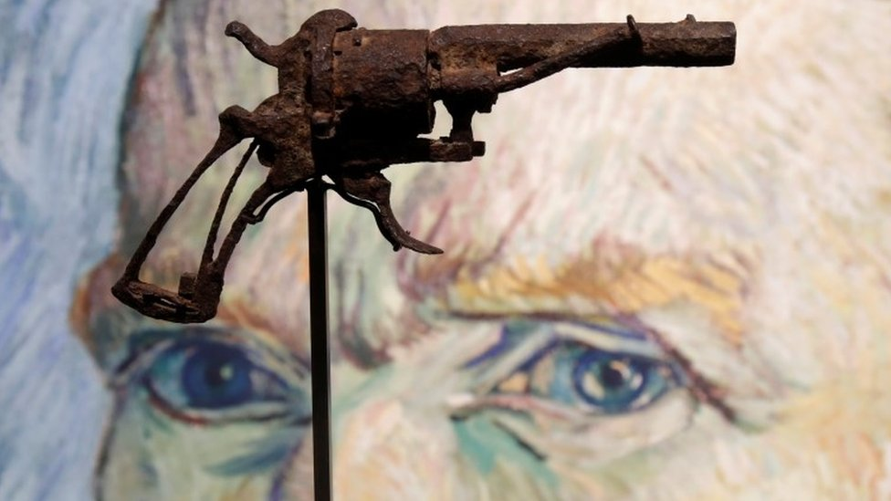 A rusted, tarnished gun raised on a display stand is seen suspended in front of a portrait of van Gogh