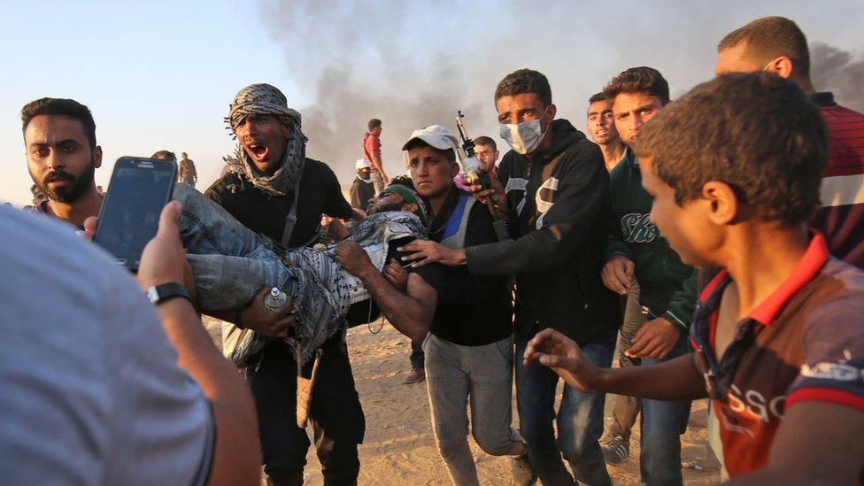 Palestinos trasladan a un herido durante las protestas del 15 de mayo