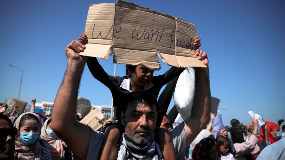"A child carries a sign reading on a man's shoulder: ""We want freedom"""