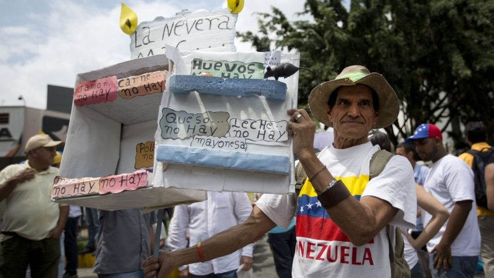 A man shows a cardboard box crafted to depict an empty refrigerator to indicate the shortage of products, during an opposition march in Caracas, Venezuela, Saturday, May 14, 2016.