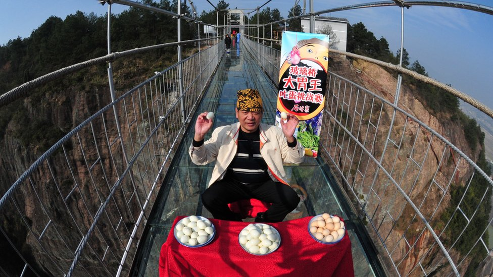 """Pan Yizhong, a man known as the """"King of Eaters"""", attempts an eating challenge on a glass-bottomed suspension bridge in Yueyang, Hunan Province Hunan province"""