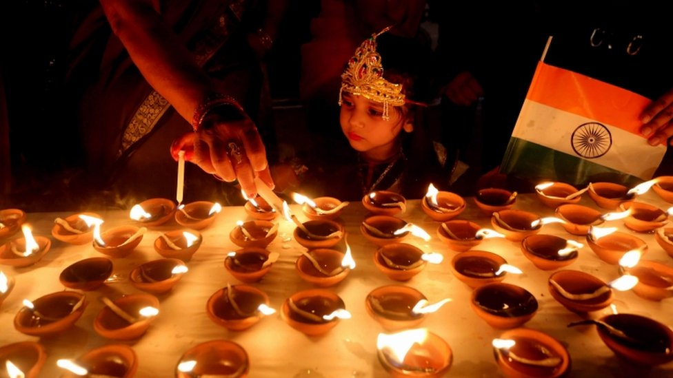 A small child looks at Diwali candles at a temple in Bhopal India
